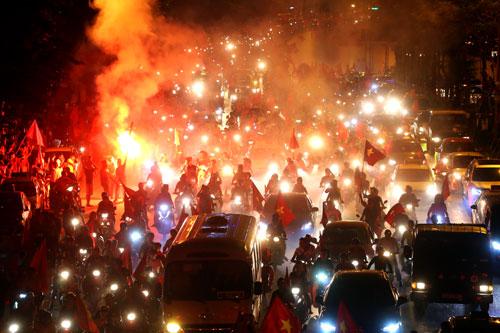 Sau trận thắng củaOlympicViệt Nam trước Syria vào tối 27/8, dòng người ở Hà Nội đổ ra đường, đốt pháo sáng ăn mừng. Ảnh: Bá Đô
