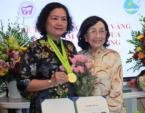 GSPhạm Thị Trân Châu, Chủ tịch Hội nữ trí thức Việt Nam (bên phải) trao Huy chương vàng cho PGS Lê Mai Hương. Ảnh: NVCC.
