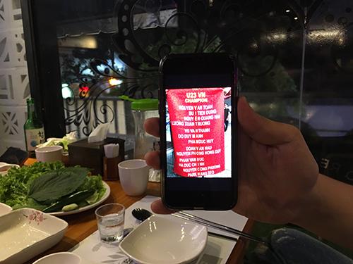 Jun-hee Han cầm điện thoại có bức ảnh U23 Việt Nam Vô địch ghép từ tên của các cầu thủ đội tuyển. Ảnh: Hạnh Phạm.