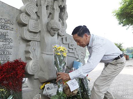 Một người dân đặt hoa viếng ông McCain tại bức tượng bên hồ Trúc Bạch. Ảnh: Ngọc Thành