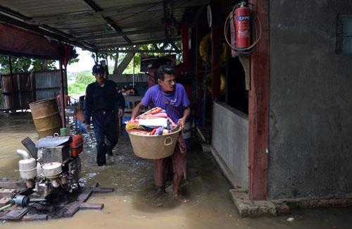 Người dân ở Bago sơ tán đồ đạc sau khi nước lũ tràn vào nhà. Ảnh: AFP.