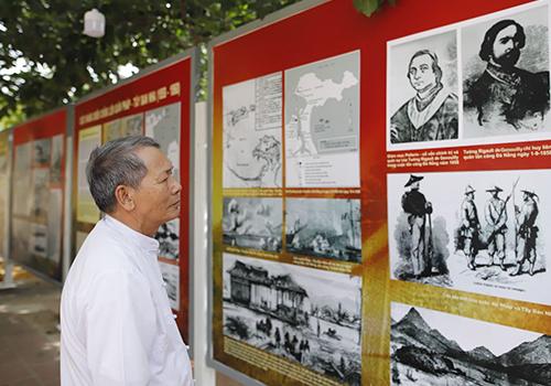 Người dân theo dõi triển lãm 160 năm liên quân Pháp - Tây Ban Nha tấn công Đà Nẵng, khai mạc tại nghĩa trũng Hoà Vang hôm 29/8. Ảnh: Nguyễn Đông.