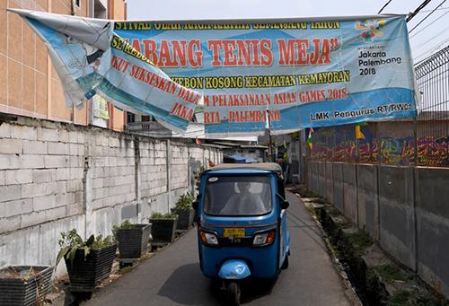 Một chiếc xe đi qua băng rôn cổ động cho Asiad ở khu ổ chuột mà Sukma sinh sống tại Jakarta. Ảnh: AFP