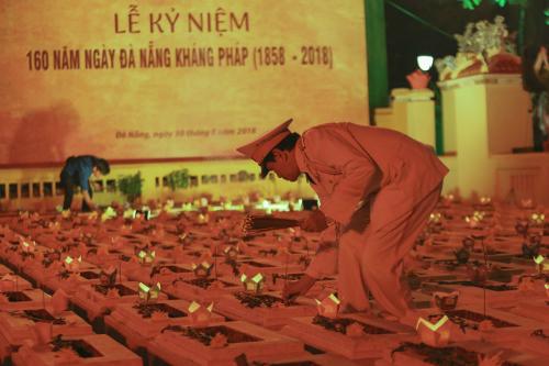 Người dân thắp hương, đặt hoa đăng lên mộ các nghĩa sỹ hi sinh trong những ngày đầu kháng Pháp tại nghĩa trũng Hoà Vang tối 30/8. Ảnh: Nguyễn Đông.