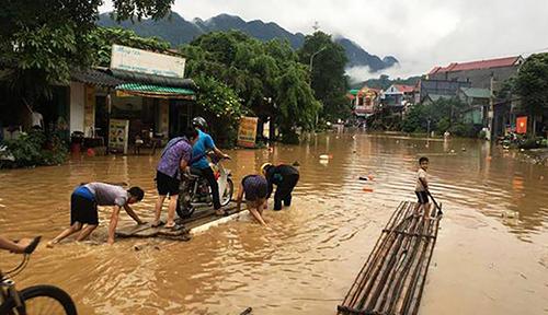 Người dân huyện Bá Thước dùng bè mảng di chuyển trên quốc lộ 217. Ảnh: Lam Sơn.