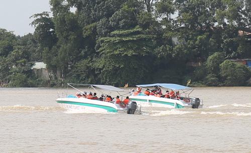 Ca nô chở du khách đang tham quan 2 bên bờ sông Đồng Nai qua TP Biên Hòa sáng nay. Ảnh: Phước Tuấn