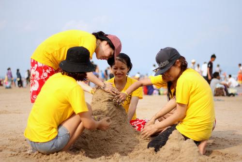 Nhóm bạn trẻ đắp cát trên bãi biển. Ảnh: Nguyễn Khoa
