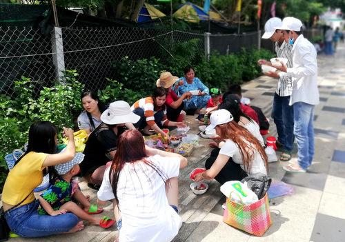 Người dân đi chơi lễ ăn trưa trên vỉa hè đường Thùy Vân. Ảnh: Nguyễn Khoa
