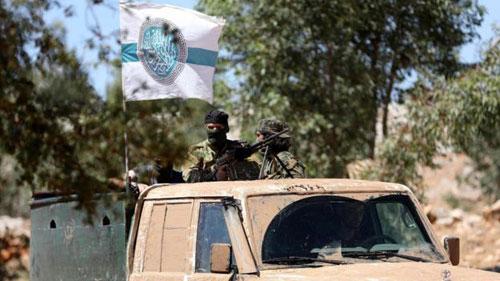 Các tay súng phiến quân trên xe bán tải cắm cờ của HTS. Ảnh: AFP.