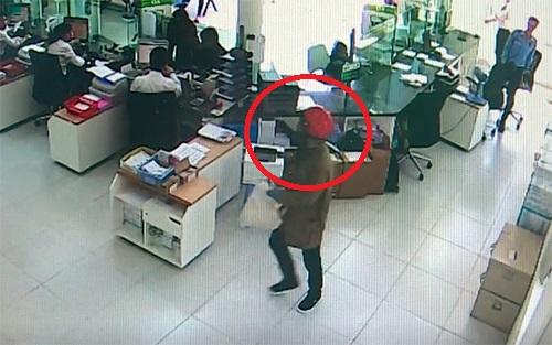 Tên cướp (khoanh tròn đỏ) cầm bao tải trắng tiến thẳng vào quầy gom tiền. Ảnh: Cắt từ camera.