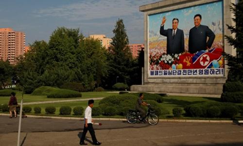 Người Triều Tiên đi qua bức tranh Kim Nhật Thành và Kim Jong-il tại Bình Nhưỡng ngày 6/9. Ảnh: Reuters.