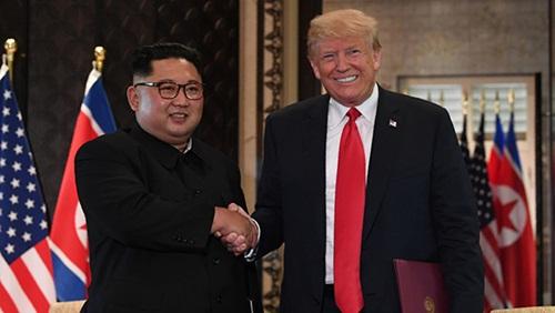 Tổng thống MỹDonald Trump (phải) bắt tay lãnh đạo Triều Tiên Kim Jong-un sau lễ ký kết tại hội nghị thượng đỉnh ở Singapore hồi tháng 6. Ảnh: AFP.
