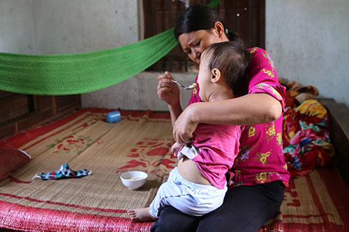 Chị Hồng chăm sóc con gái út 3 tuổi bị bãi não. Ảnh: Nguyễn Hải.