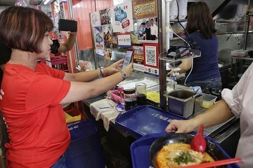 Một người quét mã QR để mua mìởTanjong Pagar Plaza Market and Food Centre, Singapore. Ảnh:Straits Times.