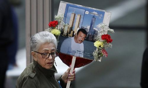 Một phụ nữ cầm tấm biển in hình người thân thiệt mạng trong vụ khủng bố 11/9 tới lễ tưởng niệm tại Trung tâm Thương mại Thế giới ở New York, Mỹ hôm nay. Ảnh: AP.