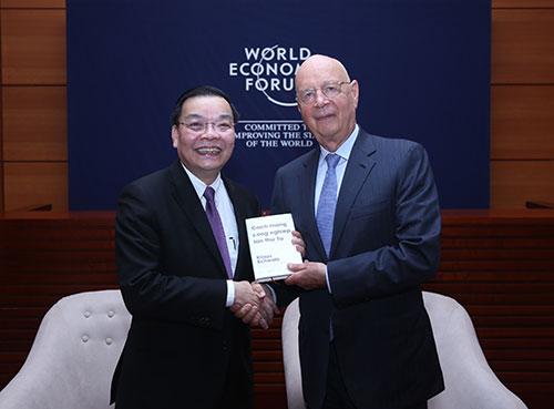 Giáo sư Klaus Schwab (bên phải)tặng Bộ trưởng Chu Ngọc Anh cuốn sách Cách mạng công nghiệp lần thứ tư. Ảnh: Trung tâm truyền thông.