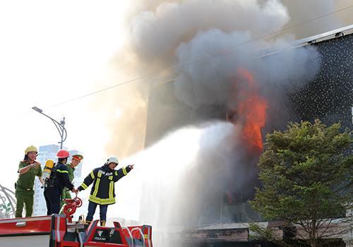 Lính cứu hoả tiếp cận dập lửa từ mặt tiền quán bar. Ảnh: Ngọc Trường.