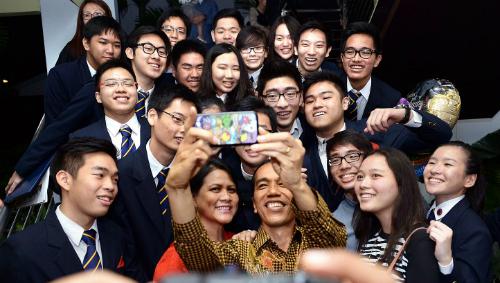 Ông Widodo và bà Iriana (áo đỏ) chụp ảnh với bạn cùng lớp của con trai tại lễ tốt nghiệp năm 2014. Ảnh: Reuters.
