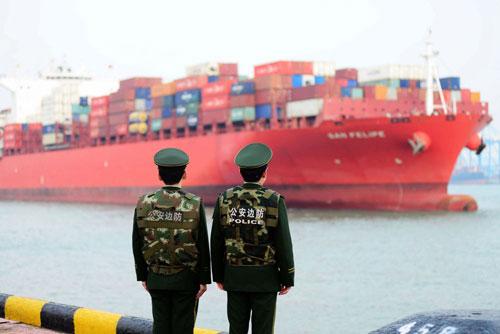 Hai cảnh sát Trung Quốc đứng gác tại một cảng biển của nước này. Ảnh: AFP.