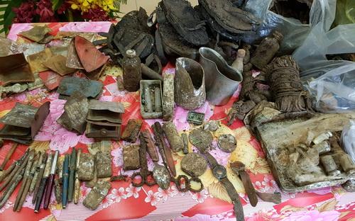 Nhiều kỷ vật được tìm thấy tại hố chôn tập thể. Ảnh: Phước Tuấn