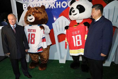 Putin (trái) và ông Tập đứng cạnh hai chú gấu linh vật của hai đội tuyểnkhúc côn cầu trên băng. Mỗi chú gấu cầm chiếc áo cầu thủ số 18 mang tên của hai lãnh đạo. Ảnh: AP.