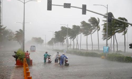 Người dân dắt xe máy qua con đường ngập lụt ở thủ đô Manila, Philippines khi siêu bão Mangkhut đổ bộ hôm nay. Ảnh: AP.