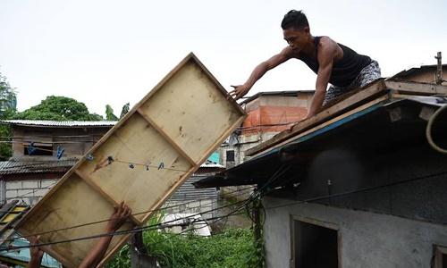 Người dân thành phố Tuguegarao, tỉnh Cagayan, gia cố nhà cửa chuẩn bị đón bão hôm 14/9. Ảnh: AFP.