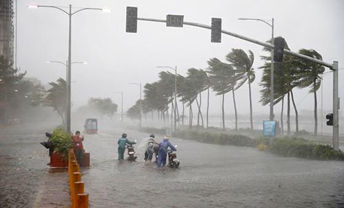 Người đi xe máy chống chọi lại mưa lớn và gió mạnh khi siêu bão Mangkhut đổ vào miền đông bắc Philippines rạng sáng ngày 15/9 tại thủ đô Manila, Philippines. Ảnh: AFP.