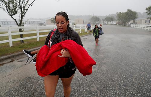 Nhân viên cứu hộ bế một đứa trẻ sơ tán khỏi vùng dân cư bị ảnh hưởng của cơn bãoFlorence ởLumberton, bang North Carolina, Mỹ vào ngày 15/9. Ảnh: Reuters.