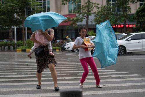 Người dân ở Quảng Đông, Trung Quốc chống chọi với gió bão Mangkhut hôm 16/9. Ảnh: AFP.