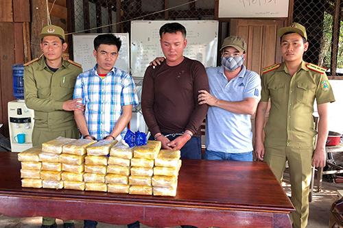 Hai người Lào bị bắt giữcùng tang vật. Ảnh: Biên phòng Quảng Trị