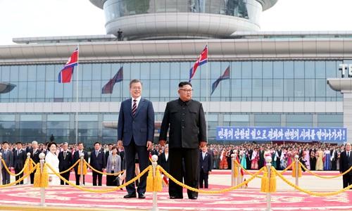 Tổng thống Hàn Quốc Moon Jae-in (trái) và lãnh đạo Triều Tiên Kim Jong-un trong lễ đón tại sân bay quốc tế Sunnan, Bình Nhưỡng, sáng 18/9. Ảnh: Reuters.
