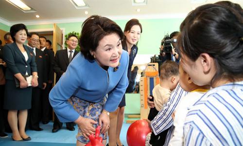 Phu nhân Kim Jung-sook (áo xanh) trò chuyện với các trẻ em tại bệnh viện Okryu trong khi phu nhân Ri Sol-ju (phải) đứng đằng sau. Ảnh:Joint Press Corps.