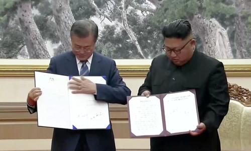 Tổng thống Hàn Quốc Moon Jae-in và lãnh đạo Triều Tiên Kim Jong-un ký tuyên bố chung tại nhà khách Paekhwawon, Bình Nhưỡnghôm nay. Ảnh: Reuters.