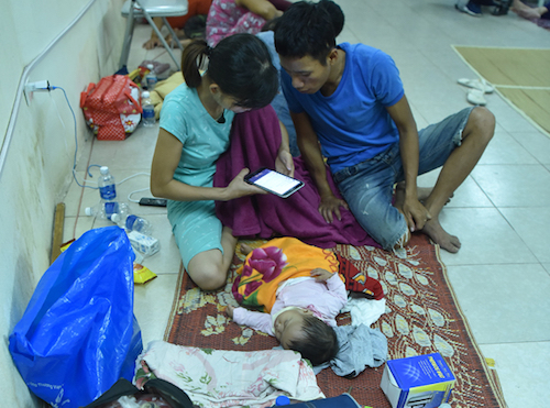 Anh Lê Văn Hưng (Nghệ An)cùng vợ, con trong đêm ngủ tạm tại nhà văn hoá. Ảnh: Giang Huy