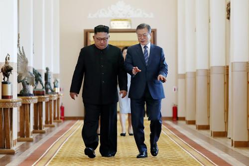 Lãnh đạo Triều Tiên Kim Jong-un (trái) và Tổng thống Hàn Quốc Moon Jae-in trao đổi khi tới phòng họp tại Bình Nhưỡng sáng nay. Ảnh: Reuters.