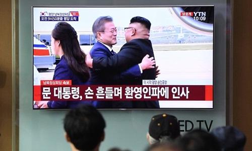 Người dân Hàn Quốc theo dõi lễ đón Tổng thống Moon Jae-in qua màn tình TV ngày 18/9. Ảnh: AFP.