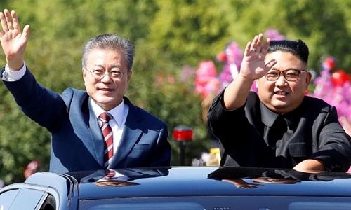 Tổng thống Hàn Quốc Moon Jae-in (trái) và lãnh đạo Triều Tiên Kim Jong-un vẫy chào người dân hai bên đường khi trên đường từ sân bay Sunan tới nhà khách Paekhwawon ngày 18/9. Ảnh: Reuters.