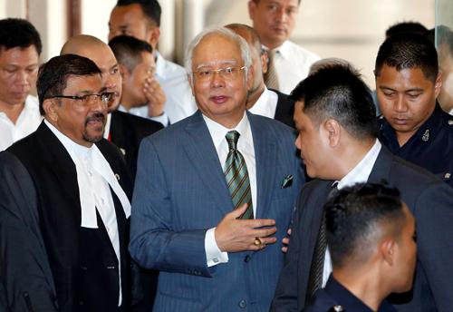Cựu thủ tướng Malaysia Najib Razak (tóc trắng) bước ra khỏi phòng xử án ở Kuala Lumpur, Malaysia hôm 8/8. Ảnh: Reuters.