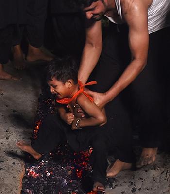 Một bé trai ở Lahore, Pakistan, sợ hãi khi bị bố đặt xuống đám than nóng trong lễ hội Ashura. Ảnh: AFP