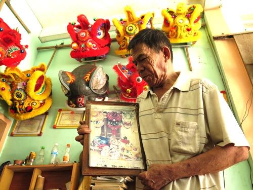 Ông Nguyễn Tô với bức ảnh chụp những con lân làm mấy chục năm trước. Ảnh: Phạm Linh.