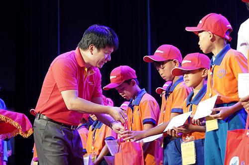 Anh Dương Hoài Nam - Giám đốc văn phòngmiền Bắc đại diện tặng quà cho các bạn nhỏ.