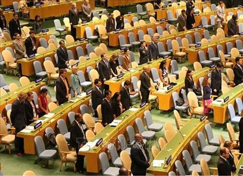 Đại diện các nước tham dự phiên họp dành một phút mặc niệm Chủ tịch nước Trần Đại Quang. Ảnh: TTXVN.