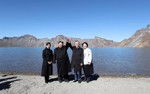 Lãnh đạo Triều - Hàn chụp ảnh lưu niệm cùng các phu nhân tại hồ nước ở miệng núi lửa Cheonji sáng 20/9. Ảnh: Reuters.