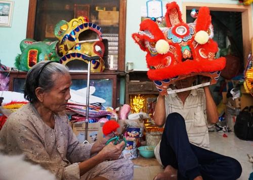 Bà Tuyết cắt râu cho đầu lân trong lúc chồng thử múa đầu lân vừa làm xong. Ảnh: Phạm Linh.