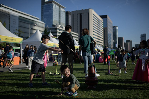 [Caption]Children play a traditional Korean game in Gwanghwamun square in Seoul on September 22, 2018. South Korea is marking the annual three-day Chuseok mid-autumn harvest festival.