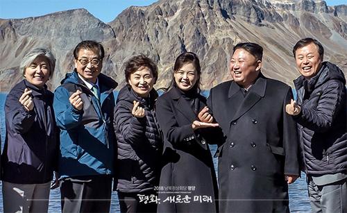 Lãnh đạo Triều Tiên Kim Jong-un (thứ hai từ phải)chụp ảnh bắn tim tại hồ nước ở miệng núi lửa Cheonji sáng 20/9. Ảnh: Twitter Nhà Xanh.