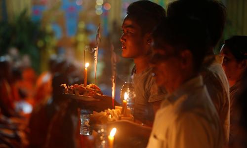 Người dân Campuchia tổ chức cúng dường và cầu nguyện cho người thân qua đời trong ngày đầu tiên của lễ Pchum Ben ở Phnom Penh hôm nay. Ảnh: Reuters.