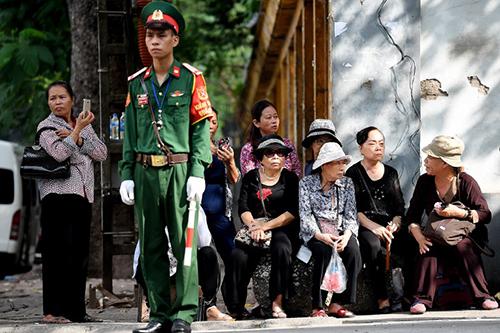 Người dân ngồi chờ bên ngoài nhà tang lễ để vào viếng Chủ tịch nước. Ảnh: AFP