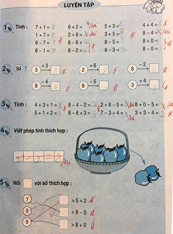 Sách Toán lớp 1 chi chít bài tập yêu cầu học sinh điền, cô giáo chữa ngay trên sách. Ảnh: Xuân Hoa